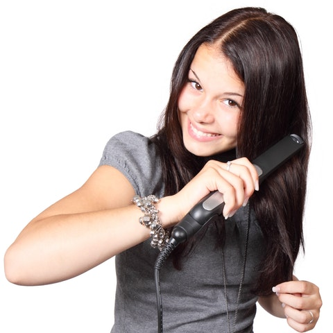 Kvinna som plattar håret